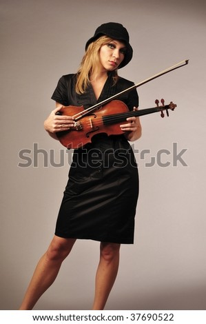 Beautiful blond violinist with her violin on gray background - stock photo