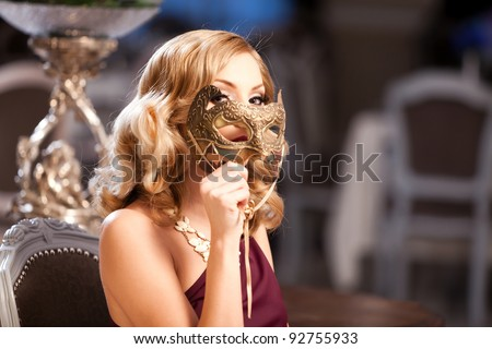 Beautiful blond with a mask in an elegant red dress. Please see more images from the same shoot. - stock photo