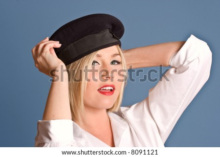 Beautiful blond with beret striking a pose, over blue - stock photo