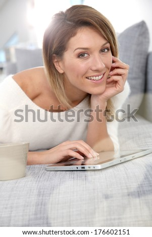 Beautiful blond woman at home websurfing on internet - stock photo
