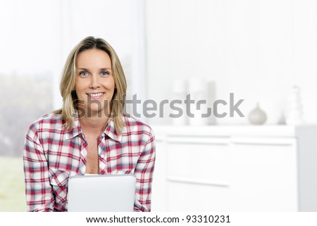 beautiful blond woman at home with tablet - stock photo