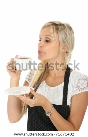 Beautiful blond woman blowing on her cup of hot tea - stock photo