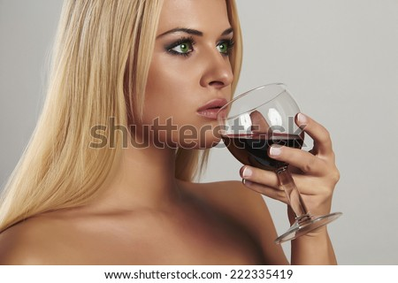 Beautiful blond woman drinking red wine.make-up.wineglass.pretty adult girl with alcohol.french manicure - stock photo