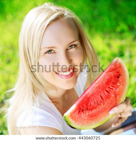 beautiful blond woman eating a watermelon in the summer park