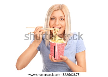 Beautiful blond woman eating Chinese noodles with sticks and looking at the camera isolated on white background - stock photo