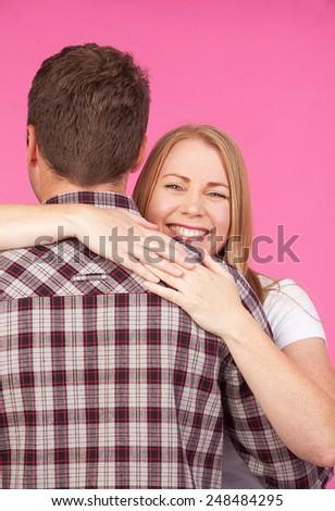 Beautiful blond Woman giving a man a big hug - stock photo