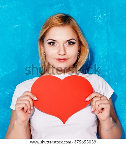 Beautiful blond woman holds in the hand a big red heart on the blue background. - stock photo