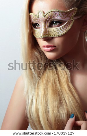 Beautiful Blond Woman in a Carnival Mask.Masquerade. Sexy Girl. Beauty & Fashion. Naked with Long Hair - stock photo