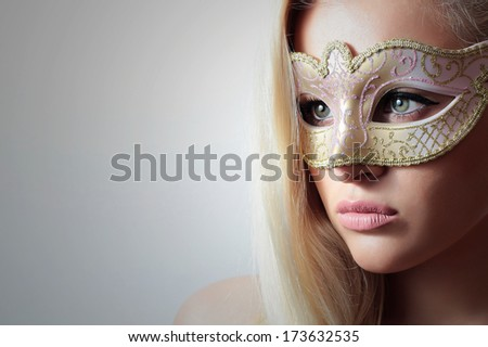 Beautiful Blond Woman in a Carnival Mask.Masquerade. Sexy Girl. Lovely. Close-up Portrait - stock photo