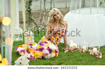 Beautiful blond woman in a dress of flowers - stock photo