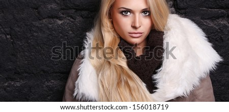 Beautiful blond woman in a fur near bricks wall. winter fashion. your text here. long hair - stock photo