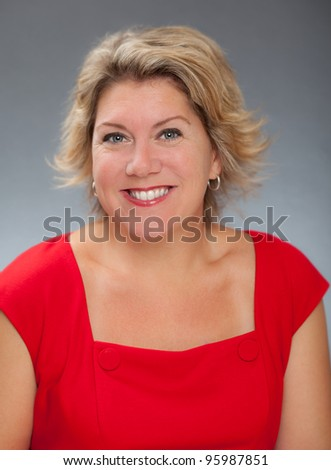 Beautiful blond woman in a red dress - stock photo
