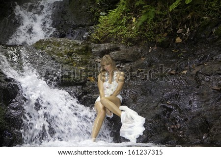 beautiful blond woman in a waterfall - stock photo