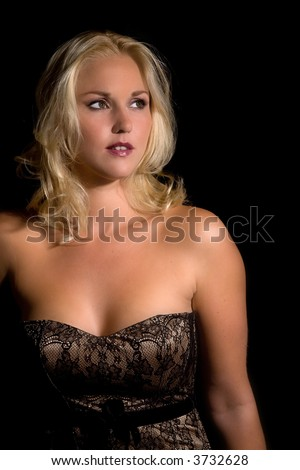 Beautiful blond woman in corset on black background - stock photo