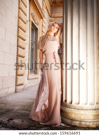 Beautiful blond woman in long dress outdoors on the stairs - stock photo