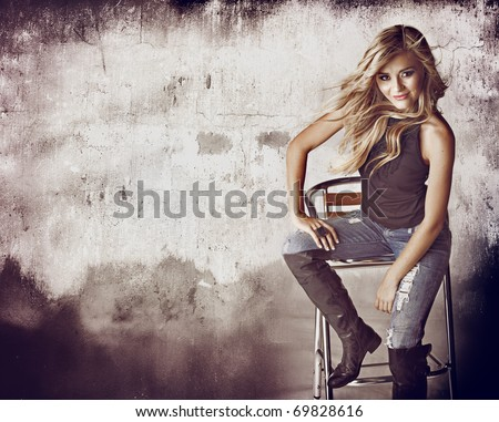 beautiful blond woman in ripped jeans and hair blowing in the wind sitting against grunge wall with space for text. - stock photo
