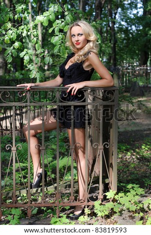 Beautiful blond woman in sexy elegant black dress, standing near the metal hedge