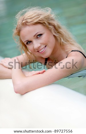 Beautiful blond woman in swimming pool - stock photo