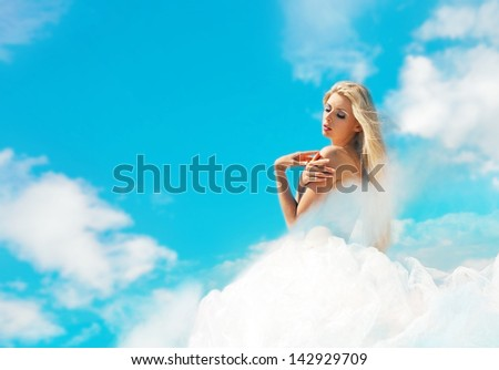 Beautiful blond woman in the cloudy sky - stock photo