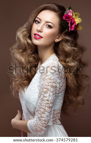 Beautiful blond woman in wedding dress with evening make-up, tender lips and curls. Bride image. Beauty face. Picture taken in the studio on a gray background - stock photo