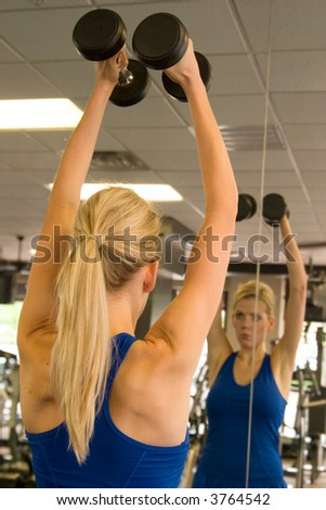 Beautiful blond woman lifting weights while looking at image in mirror in a fitness center. Image in mirror is out of focus. - stock photo