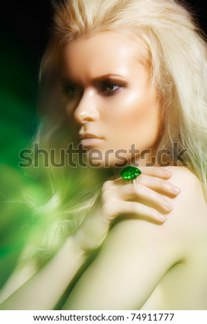 Beautiful blond woman model with big ring in magic green mist. Glamour style. Real lights effect: mixed light with long exposure. - stock photo
