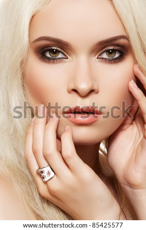 Beautiful blond woman model with brown smoky-eye make-up and white ring - stock photo