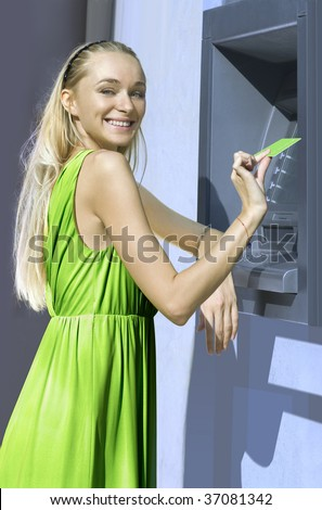 beautiful blond woman near a cash machine with plastic card
