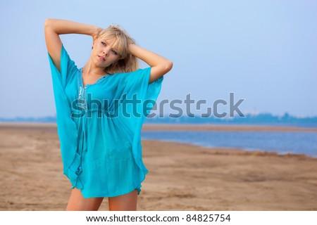 beautiful blond woman on beach wearing blue tunic - stock photo