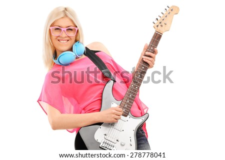 Beautiful blond woman playing an electric guitar and wearing blue headphones around her neck isolated on white background - stock photo