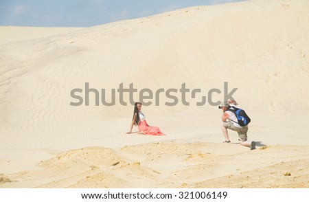 Beautiful blond woman posing in a luxurious red dress with a long train sit on land desert against  sand texture. Empty space for inscription. Cute young adult girl look at camera of photographer