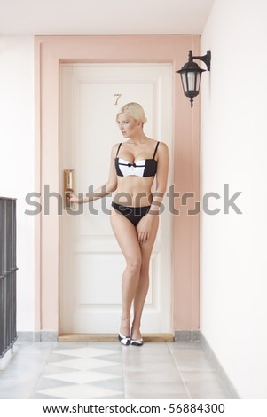 beautiful blond woman posing in front of doors with number seven - stock photo