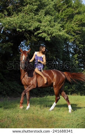 Beautiful blond woman riding horse bareback in evening field