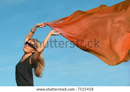 Beautiful blond woman running with a orange scarf - stock photo