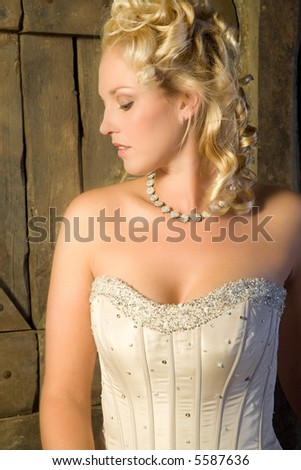 Beautiful blond woman sitting lost in thought - stock photo