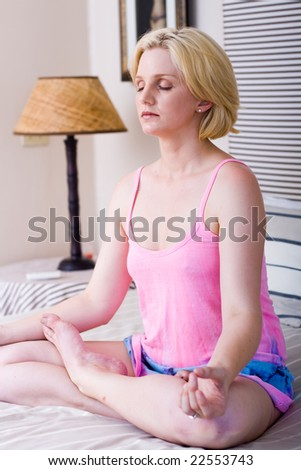 beautiful blond woman sitting on bed meditating - stock photo