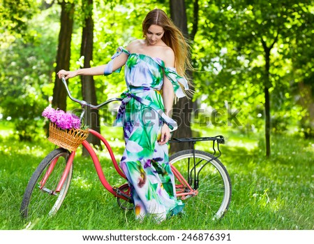 Beautiful blond woman wearing a nice dress having fun in park with bicycle carrying a beautiful basket of peony flowers. Pretty blonde girl with retro look, bike and basket with flowers - stock photo