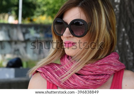 beautiful blond woman wearing big black sunglasses and pink scarf around neck outside in the park close up - stock photo