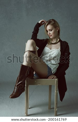 Beautiful blond woman wearing black cardigan, jean shorts and leather boots on grey studio background sitting on a rustic chair - stock photo