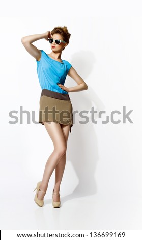 Beautiful blond woman wearing dress and glasses - stock photo