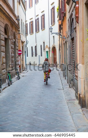 Beautiful blond woman wearing green coat, riding a bicycle - Street view of ancient city, Florence