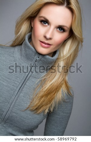 Beautiful blond woman wearing sweater - stock photo