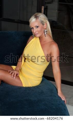 Beautiful blond woman wearing yellow dress - stock photo