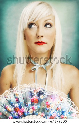 Beautiful blond woman with a delicate fan - stock photo