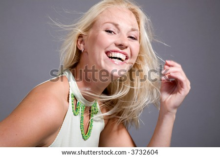 Beautiful blond woman with a happy smile on her face (some movement visible) - stock photo