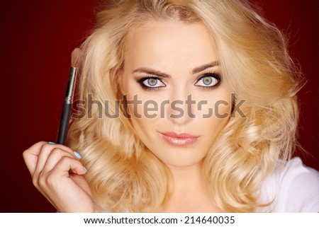 Beautiful blond woman with a quirky expression looking directly at the camera as she holds a cosmetics makeup brush in her hand - stock photo