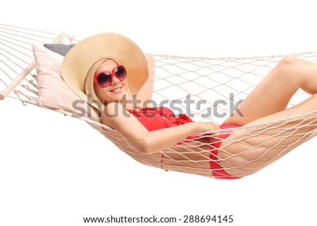 Beautiful blond woman with a stylish hat and a red bathing suit lying in a hammock and smiling isolated on white background - stock photo