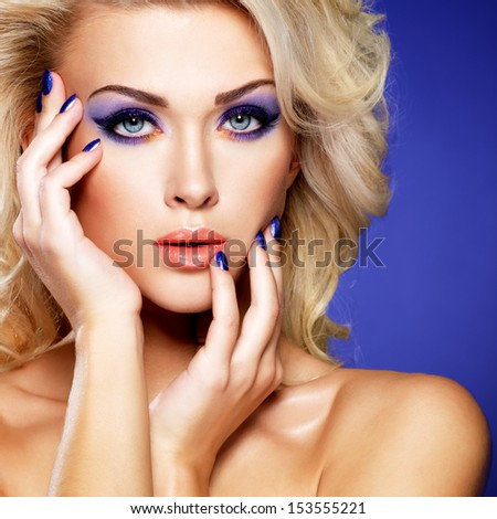 Beautiful blond woman with beauty purple manicure and makeup of eyes. Fashion model with curly hairstyle. - stock photo