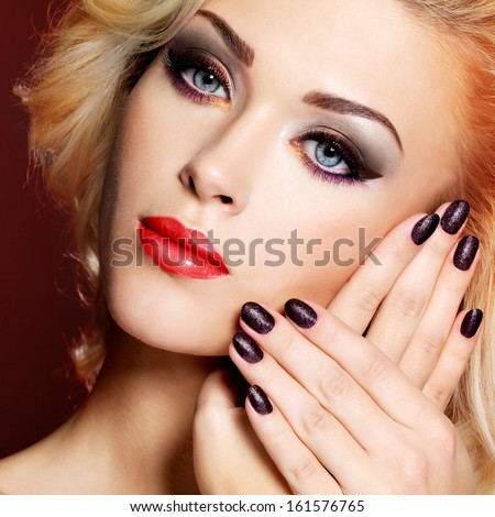 Beautiful blond woman with black nails and red lips