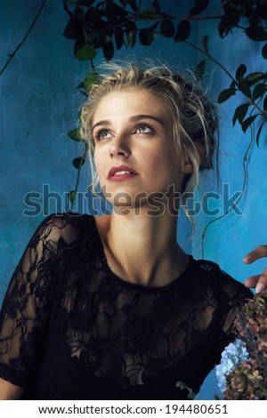 Beautiful blond woman with braid hairstyle and natural makeup. Wearing lace black dress. Against grunge blue background - stock photo